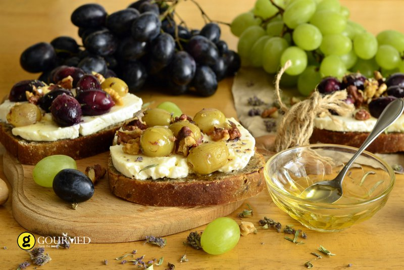Bruschetta with Greek traditional anthotyro cheese, grape, molasses and walnuts